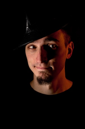 Studio portrait of skeptic looking young man in hat over black background. Low key image red lighting used photo