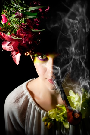 smoking pipe: Smoking pipe beautiful young fashion model with floral accessories. Artistic makeup with long feather artificial eyelashes and bright colorful eyeshadow  Stock Photo