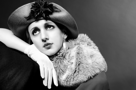 Retro styled fashion portrait of a young woman in hat. Clothing and make-up in vintage 1920s style   photo