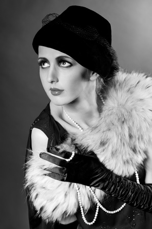 Retro styled fashion portrait of a young woman with pearls. Clothing and make-up in vintage style photo