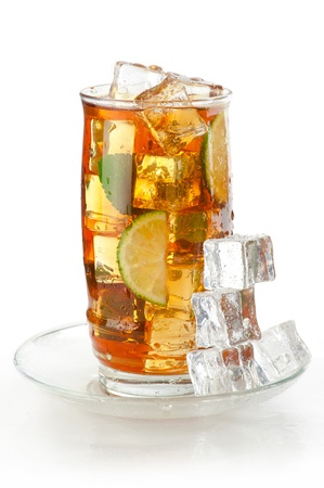 Glass of iced tea with ice cubes, lime and mint, covered with water drops on white wet surface with reflection photo