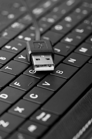 portable information device: Technology background: Macro of laptop keyboard and usb connection cable. Shallow depth of field, black and white image
