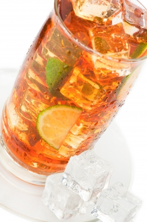 Glass of iced tea with ice cubes, lime and mint on white background photo