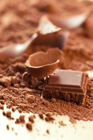 Chocolate background. Bars and strips of chocolate with cocoa powder. Shallow depth of field photo