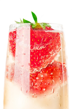 Macro shot of sparkling wine (champagne) and strawberry on white photo
