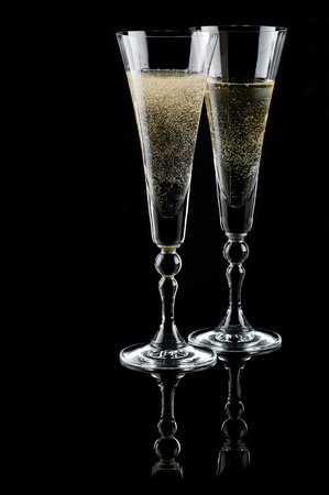 Two glasses of sparkling wine (champagne) on black photo