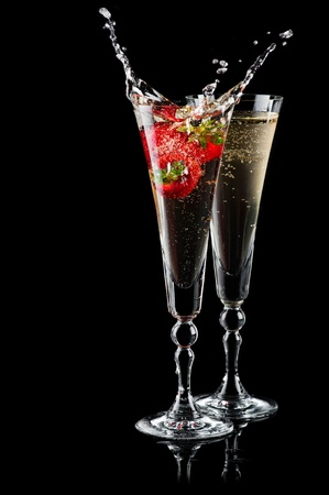 vertical bars: Two glasses of sparkling wine (champagne) with splash and strawberry on black Stock Photo