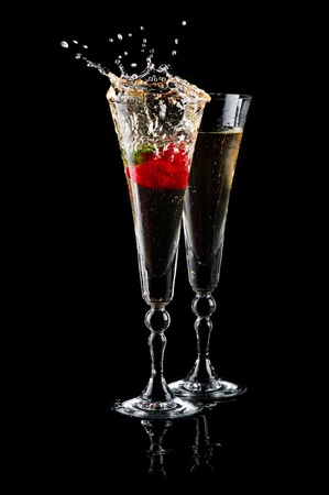 Two glasses of sparkling wine (champagne) with splash and strawberry on black photo