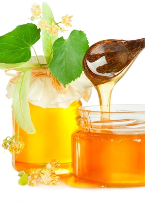 blossom honey: Fresh sweet honey, linden flowers and wooden spoon on white background Stock Photo