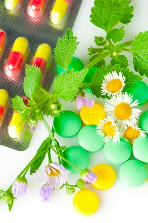 globule: Alternative medicine. Wild chamomile flowers and nettle with pills. Shallow depth of field Stock Photo