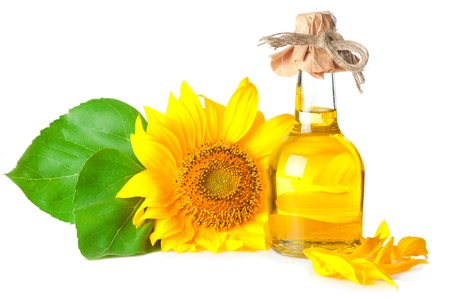 Bottle of oil and sunflower with leaves on white background