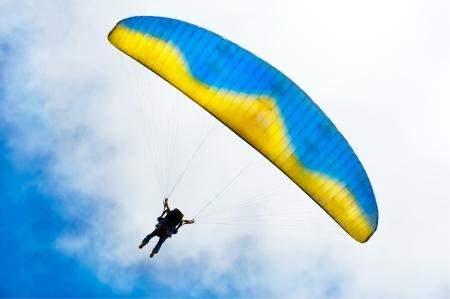 descending: Parachuter descending with instructor against blue sky Stock Photo