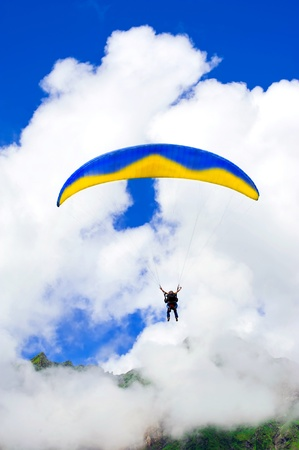 free diver: Parachuter descending with instructor in highland Himalaya mountains against blue sky Stock Photo