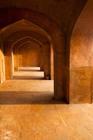 Part of ancient architecture. Corridor with arches constructed from terracotta stones photo