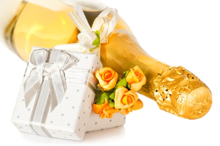 Champagne bottle, present box with bow and flower boutonniere on white background photo