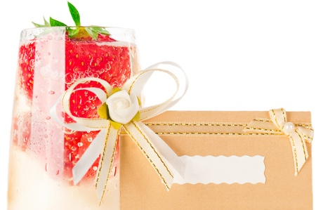 Macro glass of champagne with strawberry and event invitation card on white photo
