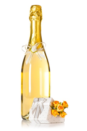 Bottle of champagne with wedding flower decoration and present box with roses on white background Фото со стока