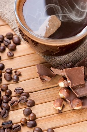 Cup of coffee, chocolate with nuts and coffee beans on wooden background with linen canvas photo