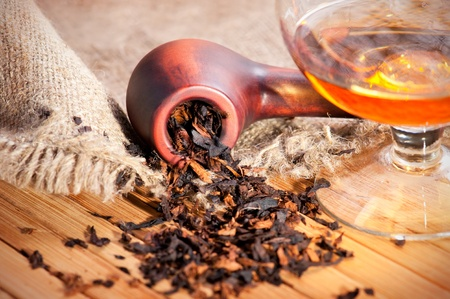 Glass of cognac and pipe with tobacco on wooden table with linen canvas Stock Photo