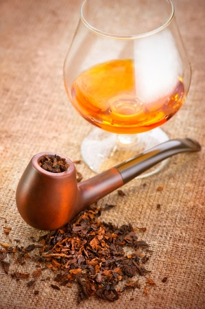 Glass of cognac and pipe with tobacco on linen canvas background photo