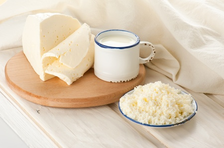 Breakfast with milk, cottage and soft sheep cheese on old wooden table with linen tablecloth photo