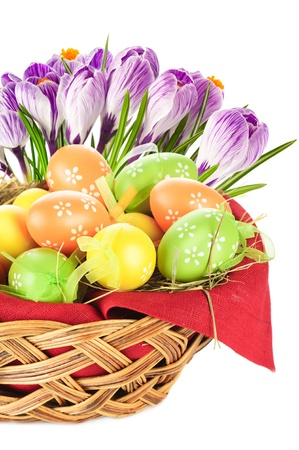 Painted easter eggs in basket and spring flowers photo