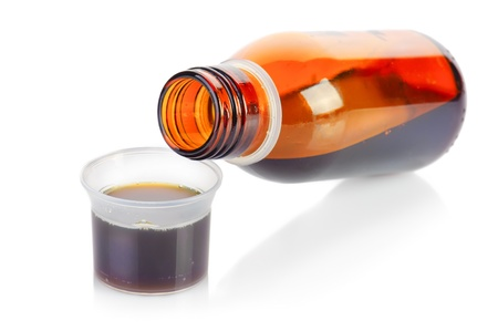 cure prevention: Bottle and plastic measuring cup of syrup medication on white background