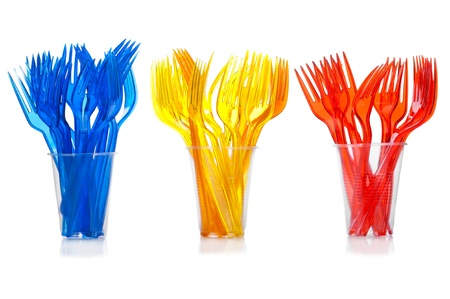 Disposable tableware. Set of colored plastic forks in transparent glasses on white background photo