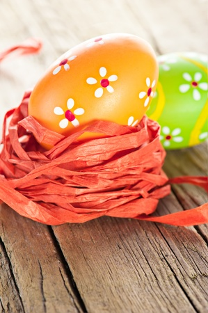 Easter background. Macro shot of painted eggs and ribbon decoration on old wooden texture photo