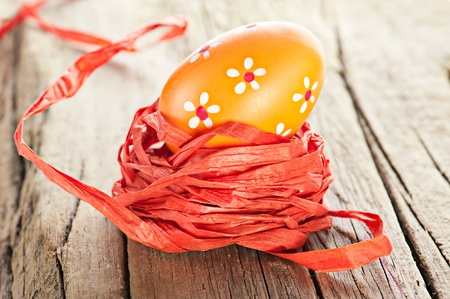 Easter background. Macro shot of painted egg and ribbon decoration on old wooden texture photo