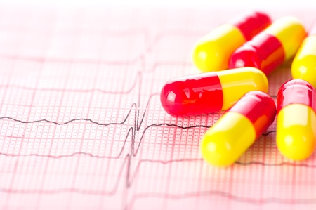 blood pressure monitor: Cardiology. Macro of ECG graph and cardio pills. Shallow depth of field