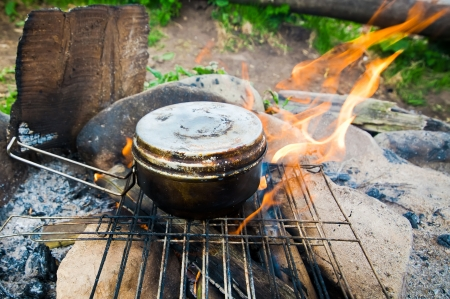 Cooking food in old tourist pot at fire place  Summer trekking activity photo