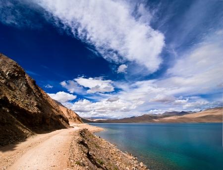 altitude: Road going along high mountain lake under blue cloudy sky  Himalaya mountains landscape panorama with Tso Moriri lake  India, Ladakh, altitude 4600 m