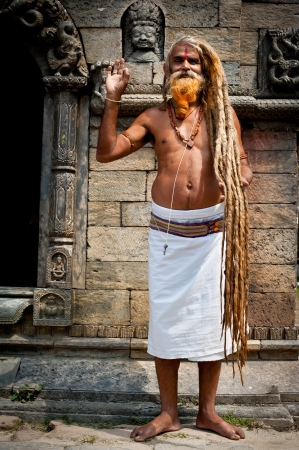 KATHMANDU, NEPAL, PASHUPATINATH TEMPLE - SEPTEMBER 21: Holy Sadhu man with dreadlocks and traditional painted face at Pashupatinath Temple. Nepal, Kathmandu. September 21, 2012