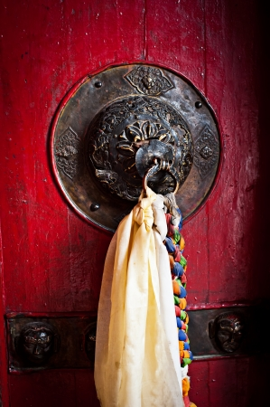 Old doorknob decorated with tassel on temple door at Buddhist monastery  India, Ladakh, Diskit monastery photo