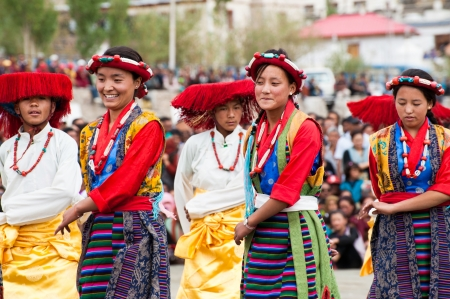 folk heritage: LEH, INDIA - SEPTEMBER 08, 2012: Young dancers in traditional Tibetan clothes performing folk dance.  Annual Festival of Ladakh Heritage in Leh, India. September 08, 2012