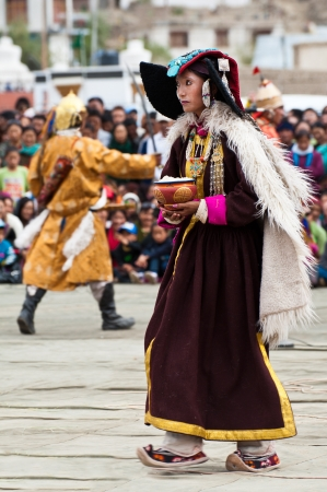 folk heritage: LEH, INDIA - SEPTEMBER 08, 2012: Woman in traditional Tibetan clothes performing folk dance.  Annual Festival of Ladakh Heritage in Leh, India. September 08, 2012