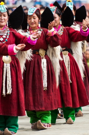LEH, INDIA - SEPTEMBER 08, 2012: Women in traditional Tibetan clothes performing folk dance.  Annual Festival of Ladakh Heritage in Leh, India. September 08, 2012
