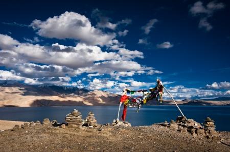 ladakh: Sunset view at Tso Moriri Lake, Stone pyramid and Buddhist praying flags. Himalaya mountains landscape with Tso Moriri lake. India, Ladakh, altitude 4600 m