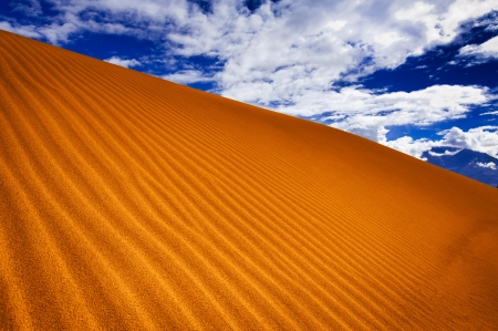 Abstract texture of sand dune in desert under blue sky photo