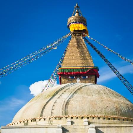 Buddhist Shrine Boudhanath Stupa with pray flags over blue sky. Nepal, Kathmandu photo