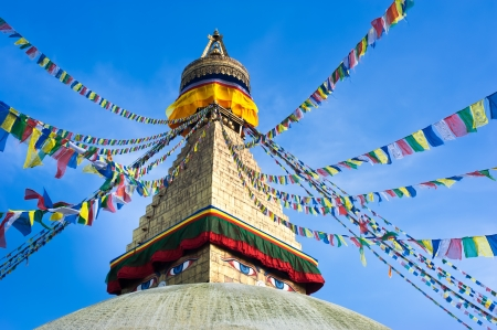 shrine: Buddhist Shrine Boudhanath Stupa with pray flags over blue sky. Nepal, Kathmandu Stock Photo