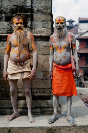 KATHMANDU, NEPAL, PASHUPATINATH TEMPLE - SEPTEMBER 21: Holy Sadhu men with traditional painted face, blessing in Pashupatinath Temple. Nepal, Kathmandu. September 21, 2012
