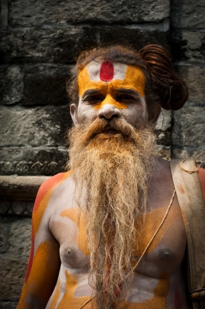 KATHMANDU, NEPAL, PASHUPATINATH TEMPLE - SEPTEMBER 21: Holy Sadhu man with traditional painted face and dreadlocks, blessing in Pashupatinath Temple. Nepal, Kathmandu. September 21, 2012