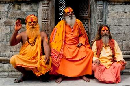 KATHMANDU, NEPAL, PASHUPATINATH TEMPLE - SEPTEMBER 21: Three Holy Sadhu men with traditional painted face, blessing in Pashupatinath Temple. Nepal, Kathmandu. September 21, 2012