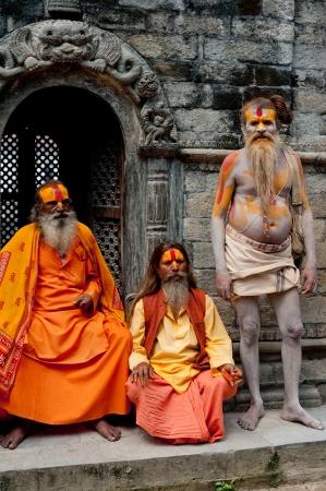 KATHMANDU, NEPAL, PASHUPATINATH TEMPLE - SEPTEMBER 21: Three Holy Sadhu men with traditional painted face, blessing in Pashupatinath Temple. Nepal, Kathmandu. September 21, 2012 Stock Photo - 16205978