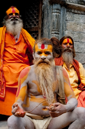 KATHMANDU, NEPAL, PASHUPATINATH TEMPLE - SEPTEMBER 21: Three Holy Sadhu men with traditional painted face, blessing in Pashupatinath Temple. Nepal, Kathmandu. September 21, 2012 Stock Photo - 16205974