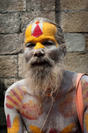 KATHMANDU, NEPAL, PASHUPATINATH TEMPLE - SEPTEMBER 21: Holy Sadhu man with traditional painted face, blessing in Pashupatinath Temple. Nepal, Kathmandu. September 21, 2012