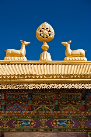 dharma: Tibetan Monastery Gates  Buddhist symbols  Dharma-wheel and deer on decorated roof under blue sky at Thiksey Gompa  India, Ladakh, Thiksey Monastery