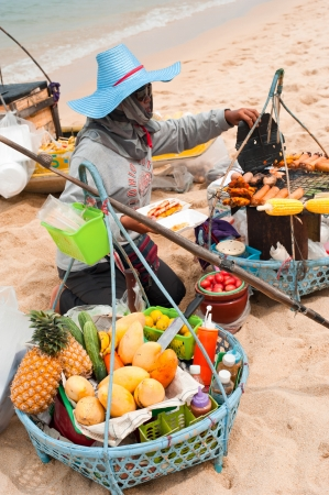 KOH SAMUI, THAILAND - MARCH 04: Thai woman selling traditional food at beach on March 04, 2013 at Samui island, Thailand. Street food cooking and selling is a local tradition, popular among tourists